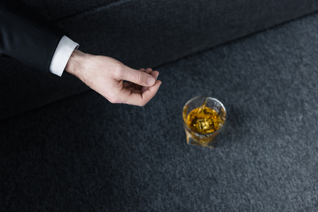 Partial view of man lying on sofa near glass of whiskey on floor Stockfoto