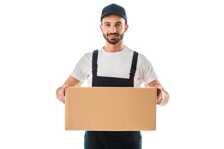 Cheerful handsome delivery man holding cardboard box and smiling at camera isolated on white background