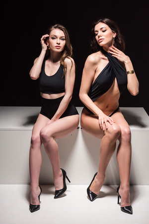 Two relaxed sexy girls in swimsuits isolated on black background