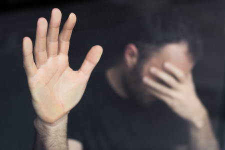 selective focus of depressed man standing by window with hand on face