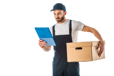 Attentive handsome delivery man holding cardboard box and looking at clipboard isolated on white background