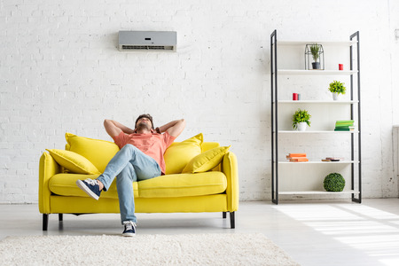 Young man sitting on yellow sofa under air conditioner in spacious apartment Stockfoto