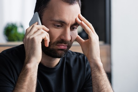 Handsome, upset man with smartphone holding hand near face Standard-Bild