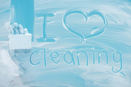 Partial view of cleaner with sponge near i love cleaning handwritten lettering on glass with white foam on blue background