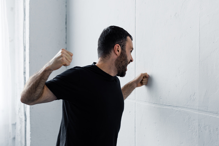 Angry bearded man in black t-shirt screaming and kicking white wall background