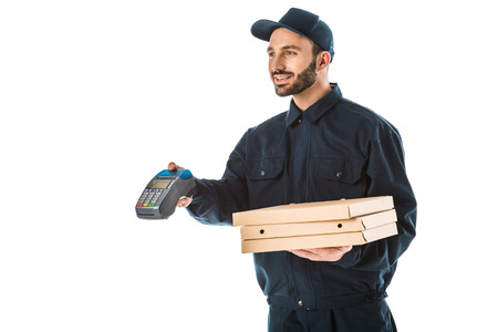 Smiling courier in overalls holding payment terminal and pizza boxes isolated on white background