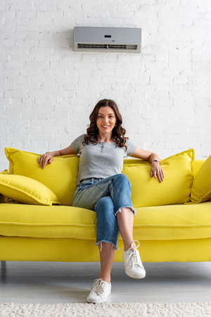 Beautiful smiling woman sitting on yellow sofa under air conditioner at home Zdjęcie Seryjne