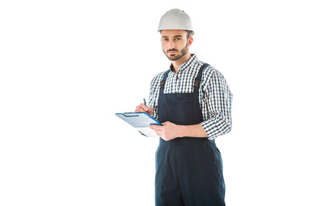Serious bearded construction worker writing on clipboard and looking at camera isolated on white background