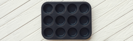 Panoramic shot of metal muffin tray on white wooden table Stockfoto