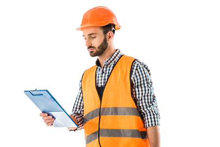 Serious construction worker in safety vest and helmet looking at clipboard isolated on white background