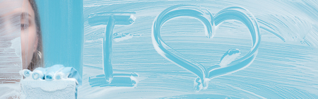 Panoramic shot of woman with sponge near i love lettering on glass with white foam on blue background