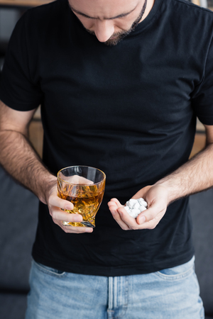 Cropped view of depressed man in black t-shirt with handful and pills and glass of whiskey