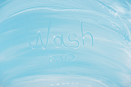 Wash me handwritten lettering written on glass with white foam on blue background