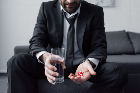 Cropped view of man in black suit holding glass of water and handful of pills