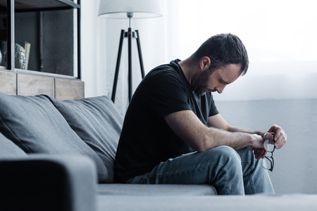 Depressed man holding glasses while sitting on grey sofa at home Stock Photo