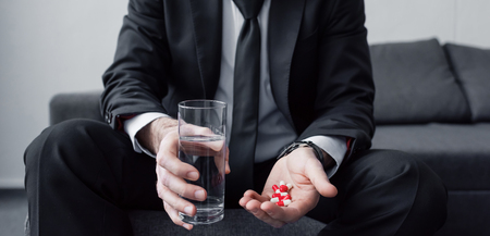 Partial view of sitting man holding glass of water and handful of pills