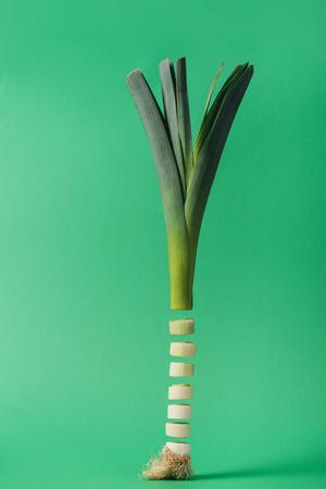 Fresh sliced organic green leek on green background