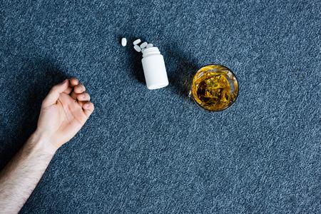 Vista recortada del hombre acostado en el piso gris cerca de un vaso de whisky y un recipiente con pastillas Foto de archivo