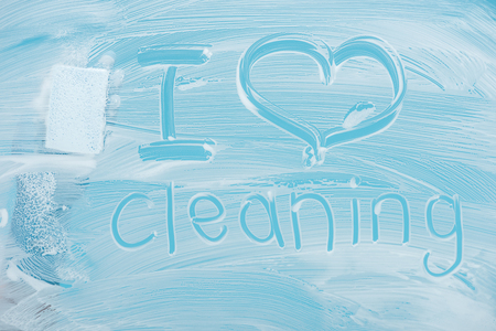 Cropped view of cleaner with sponge near i love cleaning handwritten lettering on glass with white foam on blue background
