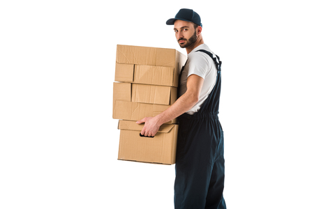 Serious delivery man carrying cardboard boxes and looking at camera isolated on white background Stock Photo