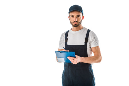 Serious delivery man writing on clipboard and looking at camera isolated on white background