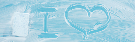 Panoramic shot of cleaner with sponge near i love handwritten lettering on glass with white foam on blue background