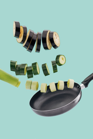 Sliced healthy organic vegetables and pan isolated on turquoise background Stock Photo