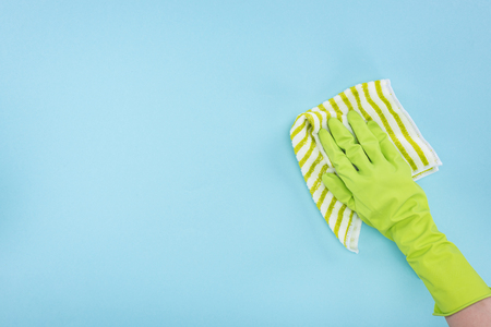 Cropped view of cleaner in green rubber glove holding striped rag on blue background