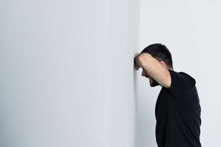 Depressed man in black t-shirt suffering while standing by white wall background