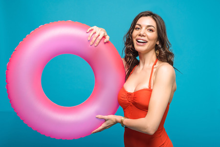 Pretty girl in swimsuit holding inflatable swim ring isolated on blue background