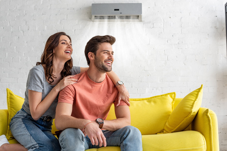 Cheerful couple sitting on yellow sofa under air conditioner at home