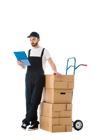 Serious delivery man standing near hand truck loaded with cardboard boxes and looking at clipboard isolated on white background