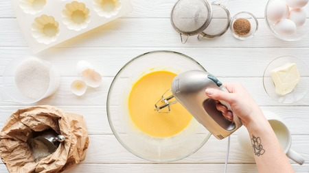 Vista ritagliata della donna che mescola l'impasto con il miscelatore manuale su un tavolo di legno con ingredienti