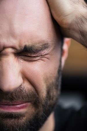 Partial view of depressed bearded man crying with closed eyes