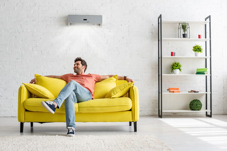 Smiling handsome man sitting on yellow sofa under air conditioner at home