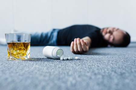 Selective focus of unconscious man lying on grey floor near glass of whiskey and container with pills
