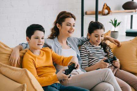 donna sorridente felice che si siede sul sofà giallo vicino ai bambini che giocano al videogioco con i joystick