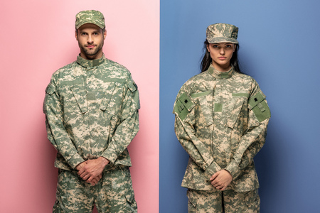 man and woman in military uniform looking at camera on blue and pink