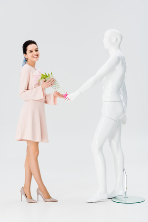 beautiful smiling girl with mannequin and flower bouquet isolated on grey