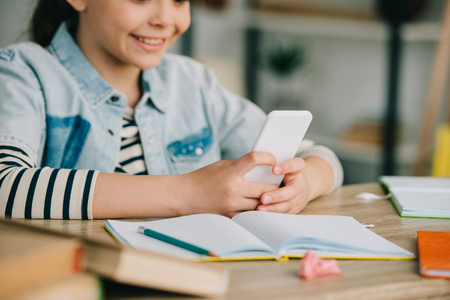 partial view of smiling child using smartphone while sitting at desk and doing schoolwork at home