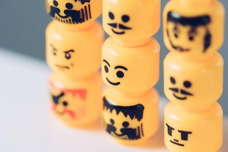 KYIV, UKRAINE - MARCH 15, 2019: Selective Focus of yellow heads of lego figurines with various faces in rows Stockfoto