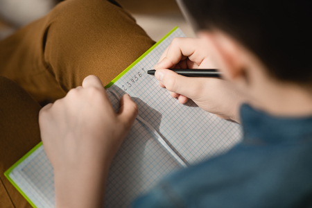 selective focus of schoolboy writing in copy book while making schoolwork at home