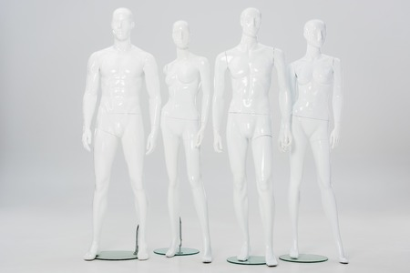 white plastic mannequins in row on grey
