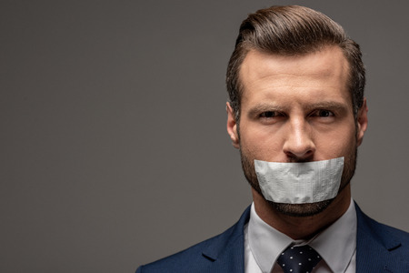 handsome businessman in suit with duct tape on mouth on grey with copy space