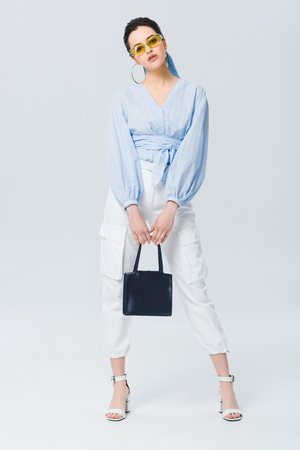 beautiful stylish girl with bag looking at camera and posing on grey