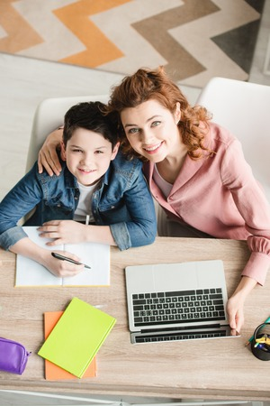 top view of happy mother hugging adorable son while sitting at table near laptop and looking at camera
