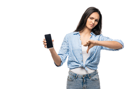 disappointed girl holding smartphone with blank screen and showing thumb down Isolated On White Foto de archivo - 123588515