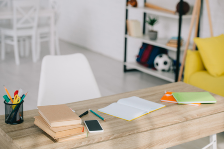 selective focus of wooden desk with books, stationery, copy books and smartphone with blank screen Stock Photo