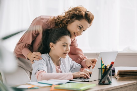 happy mother helping smiling daughter doing schoolwork at home