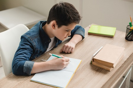 high angle view of attentive boy writing in copy book while doing schoolwork at home